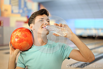 Man holds ball and drinks water in bowling club