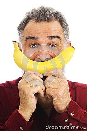 Man holds banana to face, imitating smile