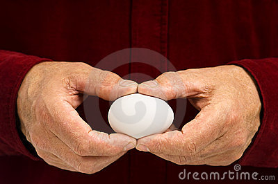 Man holds blank white egg.