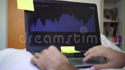 A man at home with a laptop is watching a financial graph. Investing, stock exchange.  stock video footage