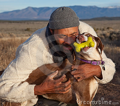 Man hugging and playing with his dog