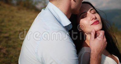 Man hugs brunette woman tender and kisses her forehead sitting on the top of a mountain.  stock footage