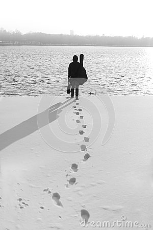 Free Man In Black With Suitcase And Guitar Walking Towards Water In Winter Season Royalty Free Stock Image - 103660556