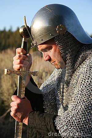 Free Man In Chain Mail Kneeling And Gripping A Sword Stock Image - 9868531