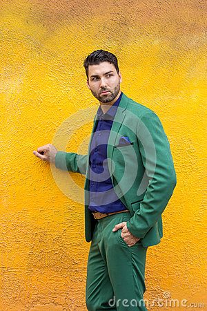 Free Man In Gren Suit On Yellow Wall Background. Royalty Free Stock Image - 75556206