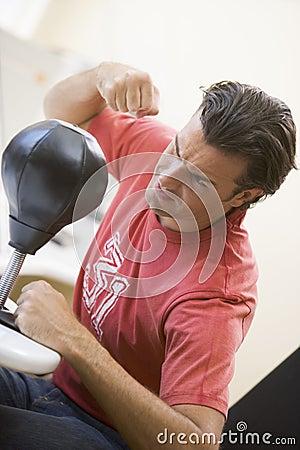 Man indoors using small punching bag