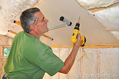 Man installing drywall on ceiling
