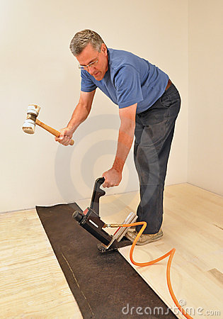 Man installing hardwood floor using nailer