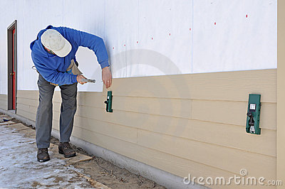 Man installing siding using gauges