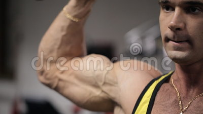 Man with an intense expression on his face training in the gym his biceps and triceps stock video footage
