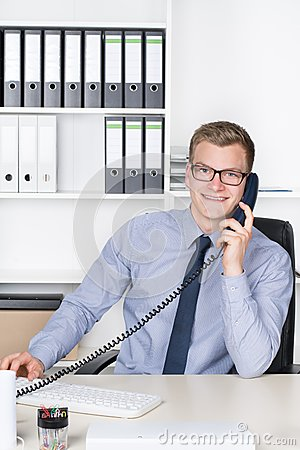 Free Man Is Phoning At The Desk In The Office Royalty Free Stock Image - 41692666