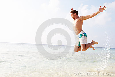 Man Jumping In The Air On Tropical Beach