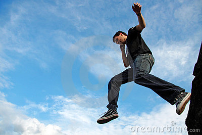 Man jumping from stone edge