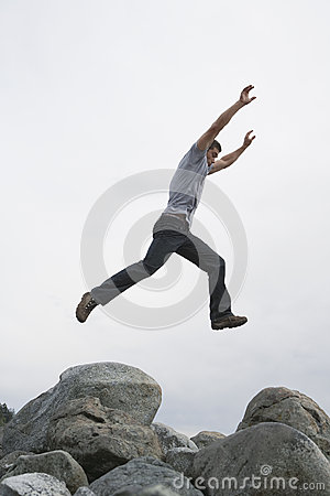 Free Man Jumping With Arms Raised Over Rock Royalty Free Stock Photo - 33812655