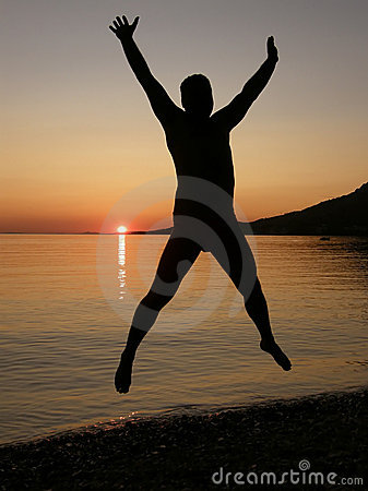 Man jumps in sunset at sea