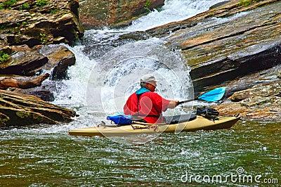 Man in Kayak at a Waterfall