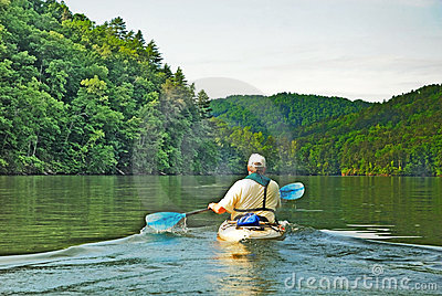 Man Kayaking on Quiet Lake