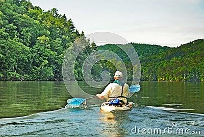Man Kayaking on Quiet Lake