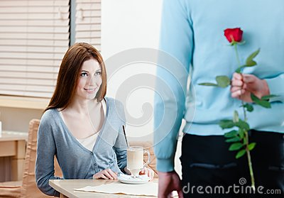 Man keeps crimson rose behind his back