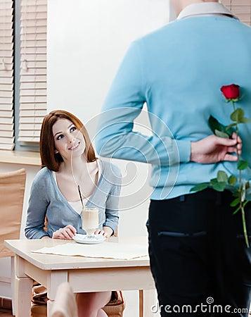 Man keeps red rose behind his back
