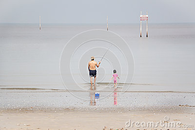 Man and kid walking towards the sea to fish