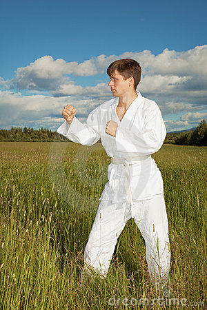 Man in kimono standing in grass