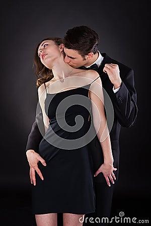 man kissing woman  neck  removing dress strap stock photo image