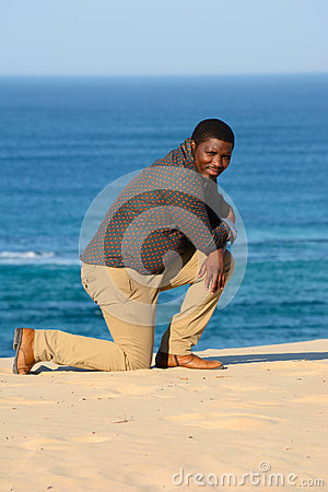Man kneeling on beach