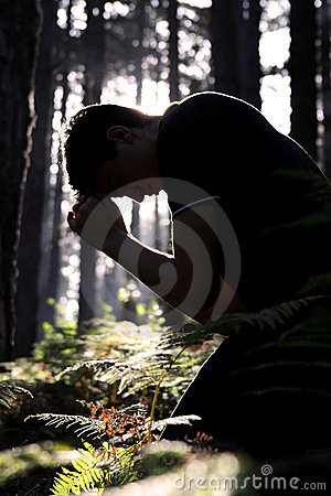 Man kneeling and praying in the forest