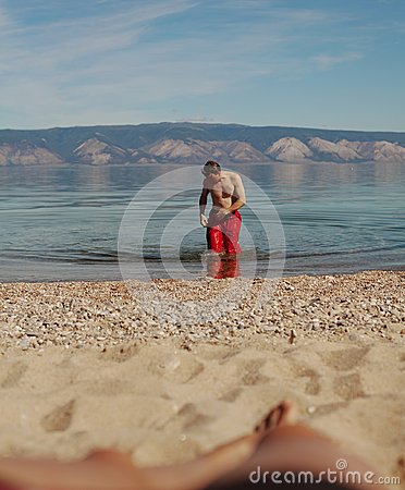 Young man walking out of Lake Baikal to beach on Olkhon Islands ...