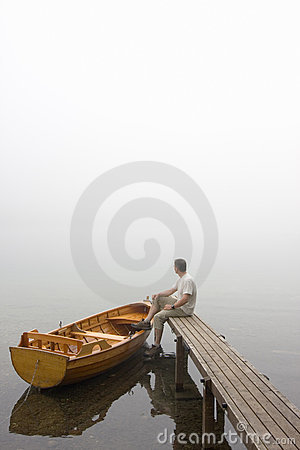 Man at a lake on misty morning