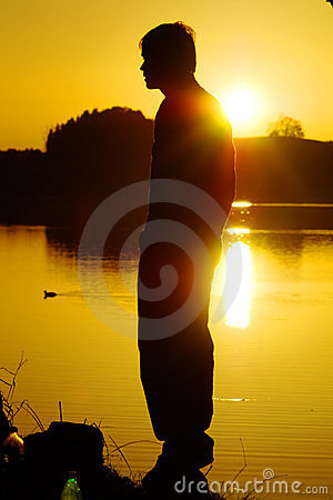 Man by lake at sunset