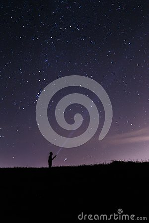 Man with a lantern under a starry night sky Stock Photo