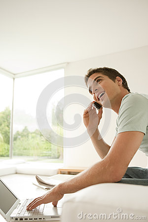 Man with Laptop and Cell at Home