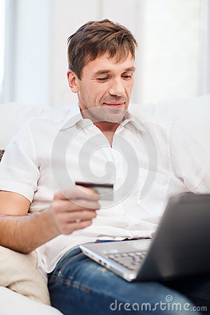 Man with laptop and credit card at home