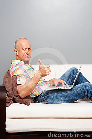 Man with laptop at home showing thumbs up