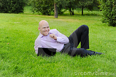 Man with laptop lying on green grass