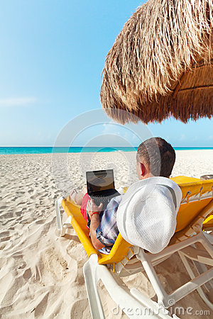 Man with laptop relaxing on the deckchair