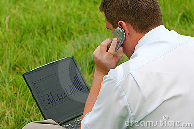 Man with laptop sitting in grass