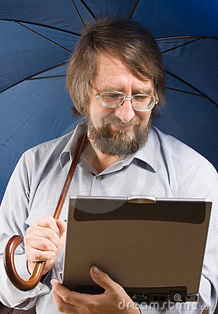 Man with laptop under umbrella