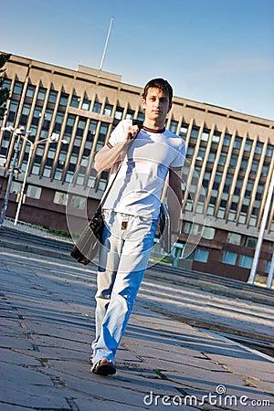 Man with laptop walking along the street