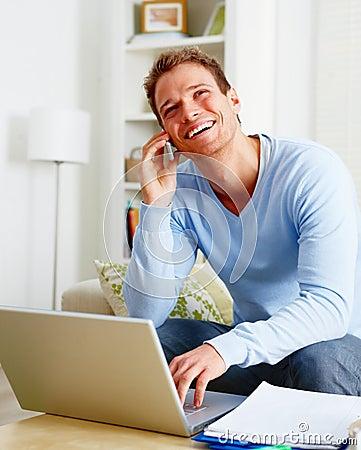 Man laughing joyfully talking on mobile phone
