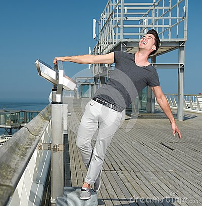 Man laughing outdoors with open arms