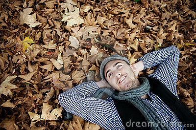 Man laying on autumn leaves.
