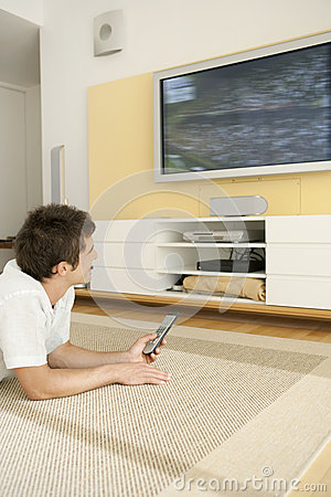 Man Laying Down on Floor Watching TV