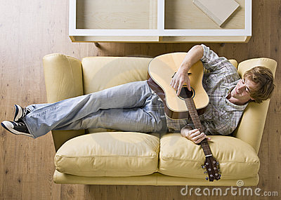 Man laying on sofa playing guitar