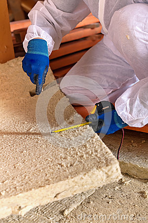 Man laying thermal insulation layer closeup stock photo for Mineral wool installation