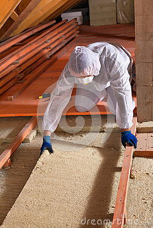 Man laying thermal insulation layer wearing protective for Mineral wool installation