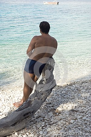 Man leang on tree on a pebbly beach in Paxos Greec