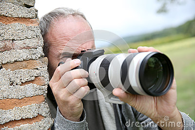 Man leaning on wall taking pictures outdoor